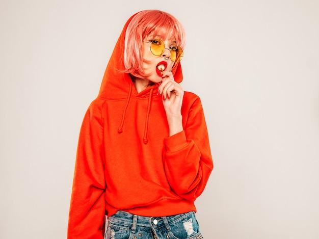 Портрет молодой красивой битник плохая девушка в модном красном летнем балахоне и серьги в носу. сексуальная беззаботная улыбающаяся белокурая женщина позирует в студии в парике. позитивная модель лижет круглую леденец Бесплатные Фотографии