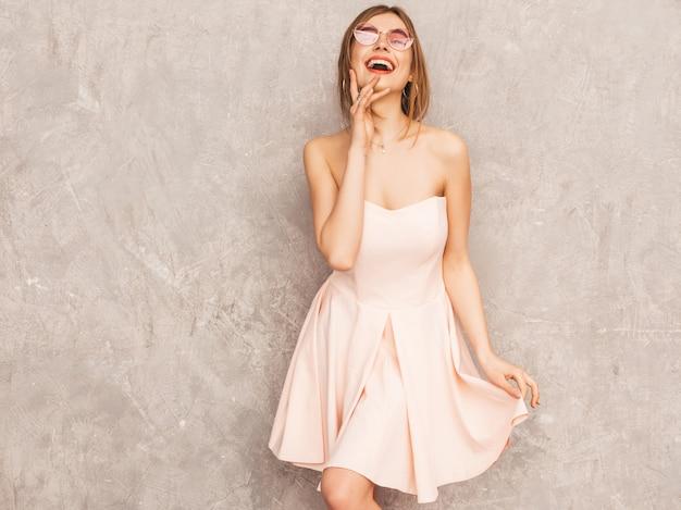 Портрет молодой красивой улыбающейся девушки в модном летнем светло-розовом платье. сексуальная беззаботная женщина позирует. позитивная модель с удовольствием. танцы в круглых очках Бесплатные Фотографии