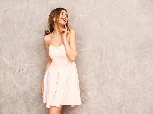 유행 여름 빛 핑크 드레스에 젊은 아름 다운 웃는 여자의 초상화. 섹시 평온한 여자 포즈입니다. 긍정적 인 모델 재미. 생각 무료 사진