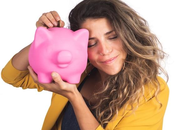 スタジオで貯金箱を保持している若い美しい女性の肖像画。孤立した白い背景。お金を節約するコンセプト。 無料写真