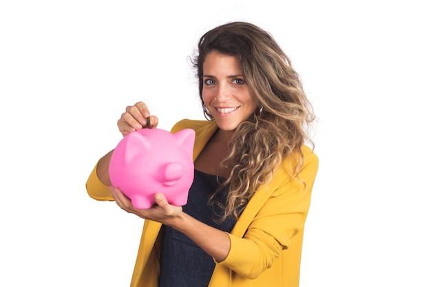 Портрет молодой красивой женщины, держащей копилку на студии. экономьте деньги концепции. Бесплатные Фотографии