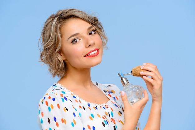 Портрет молодой красивой женщины с духами над голубой стеной Бесплатные Фотографии