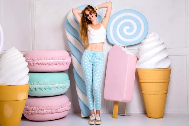 かわいいトレンディなパジャマと大きなお菓子に囲まれたサングラスを身に着けている長い髪の若いブロンドの女性の肖像画 無料写真