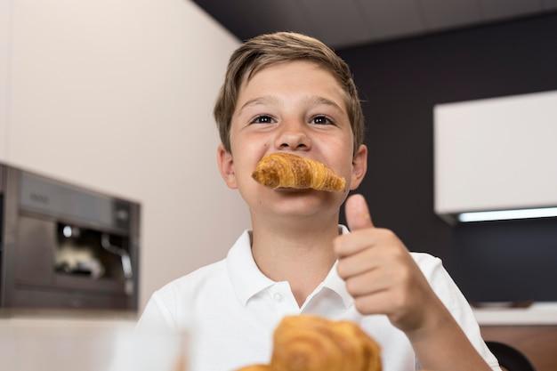 크로와상을 먹는 어린 소년의 초상화 무료 사진