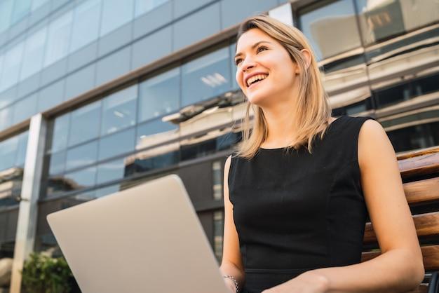 Портрет молодой деловой женщины, используя свой ноутбук, сидя на открытом воздухе на улице. бизнес-концепция. Бесплатные Фотографии