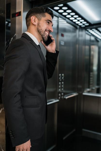 호텔 엘리베이터에서 전화 통화하는 젊은 사업가의 초상화. 비즈니스 여행 개념. 무료 사진