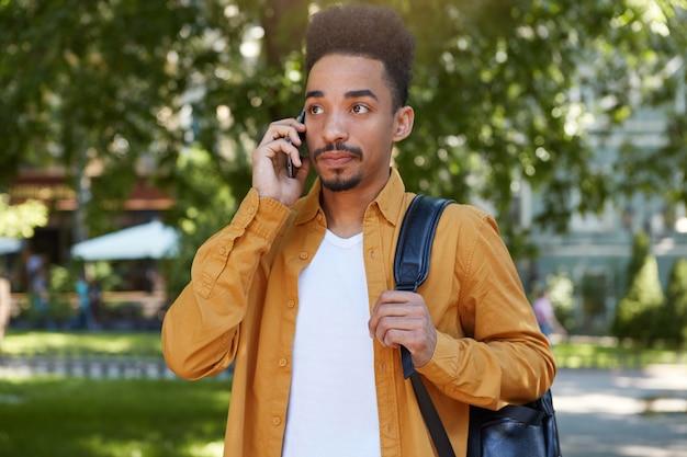Портрет молодой спокойный темнокожий мужчина в желтой рубашке гуляет по парку, держит телефон, ждет ответа от своей подруги, задумчиво смотрит. Бесплатные Фотографии