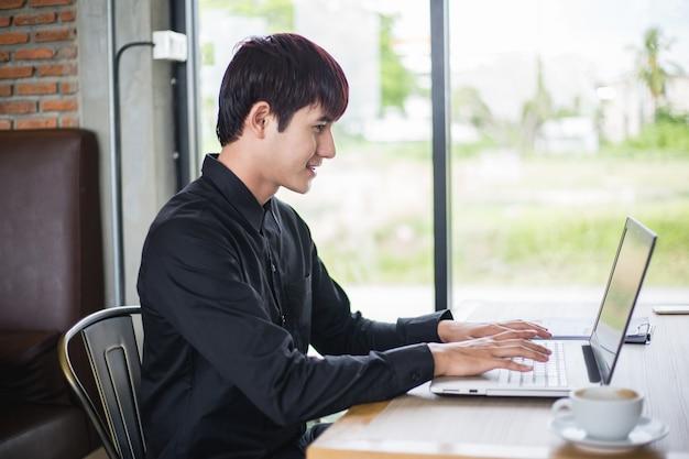 Портрет молодой случайный бизнесмен отдохнуть и сидит в кафе и работает на своем ноутбуке Premium Фотографии