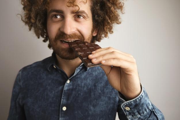 Портрет молодого кавказского человека с вьющимися волосами, счастливым со здоровой кожей, кусает органическую свежеиспеченную плитку шоколада стороной рта, глядя в сторону камеры Бесплатные Фотографии