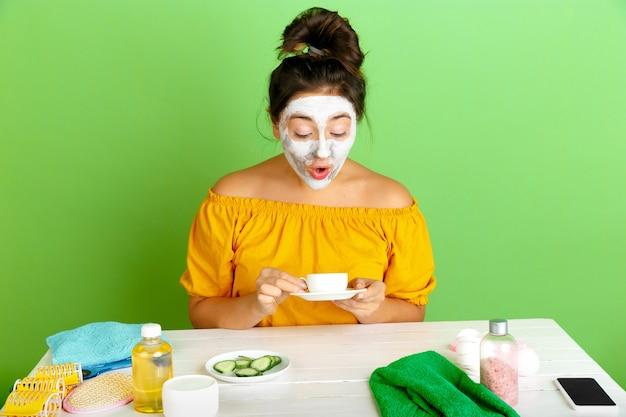 Портрет молодой кавказской женщины в день красоты, уход за кожей и волосами. женская модель пьет кофе, чай, применяя маску для лица. удивлен. уход за собой, естественная красота и концепция косметики. Бесплатные Фотографии