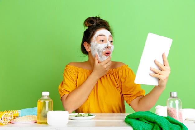 Портрет молодой кавказской женщины в день красоты, уход за кожей и волосами. женская модель делает селфи, видеоблог или видеозвонок, применяя маску для лица. уход за собой, естественная красота и концепция косметики. Бесплатные Фотографии