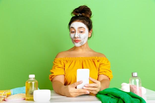 아름다움의 날, 피부와 헤어 케어 루틴에서 젊은 백인 여자의 초상화. 얼굴 마스크를 적용하는 동안 셀카를 만드는 천연 화장품으로 여성 모델. 몸과 얼굴 관리, 자연의 아름다움 개념. 무료 사진