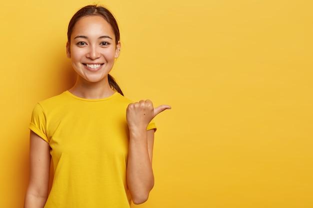 쾌활한 젊은 아시아 여성의 초상화는 엄지 손가락, 행복한 얼굴 표정으로 멀리 떨어져 있으며 광고 복사 공간을 보여주고 쾌적한 외모를 가지고 있으며 밝은 노란색 옷을 입습니다. 무료 사진
