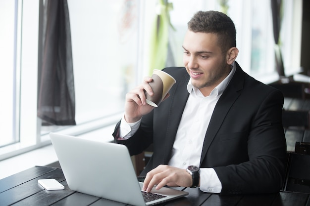 Portrait of young cheerful businessman working at wooden table in modern coffee shop Free Photo