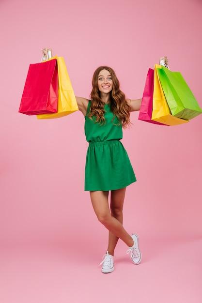 화려한 쇼핑 가방을 들고 녹색 드레스에 젊은 명랑 판독 헤드 곱슬 여자의 초상화 무료 사진