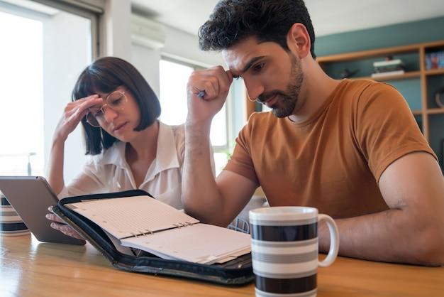 Портрет молодой пары расчета и оплаты счетов на цифровом планшете из дома. пара планирует ежемесячный бюджет. Бесплатные Фотографии