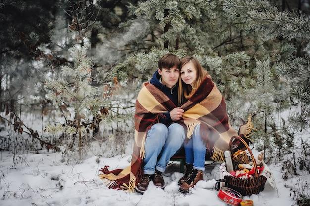 Портрет молодой пары в одеяле на пикнике в день святого валентина в заснеженном парке. человек обнимает девушку в лесу. концепция глинтвейн, горячий чай, кофе. рождественский праздник, праздник. с новым годом. Premium Фотографии