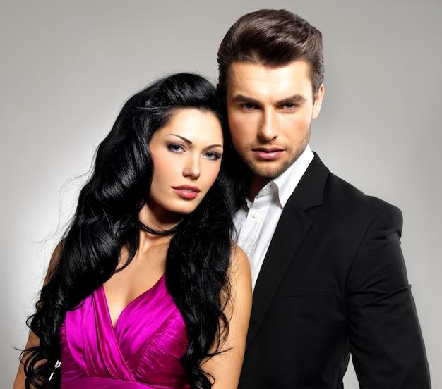 Портрет молодой влюбленной пары, позирующей в студии, одетой в классическую одежду Бесплатные Фотографии
