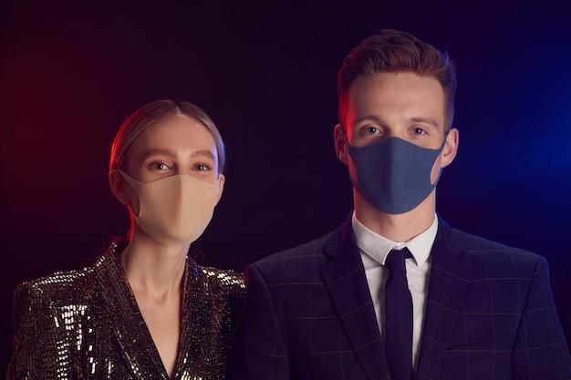 フェイスマスクを着用し、黒い背景に立っているパーティーでポーズをとっている間カメラを見ている若いカップルの肖像画 Premium写真