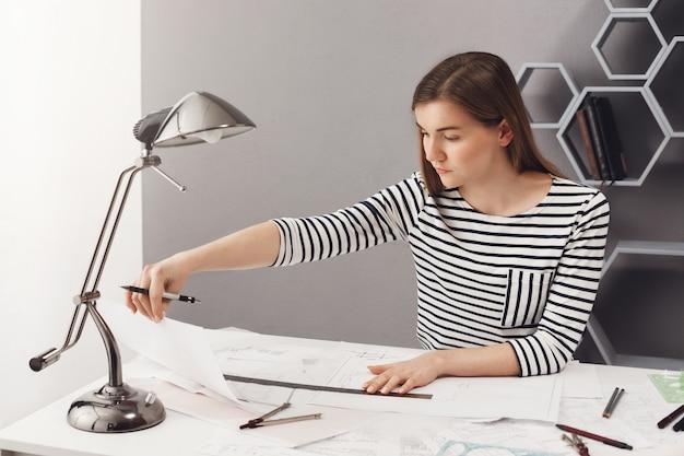 Портрет молодой темноволосый студент девушка с длинными волосами в полосатой рубашке, сидя за столом в доме, делая архитектор проект для экзаменов, глядя на рисунки с сосредоточенным выражением лица. Бесплатные Фотографии