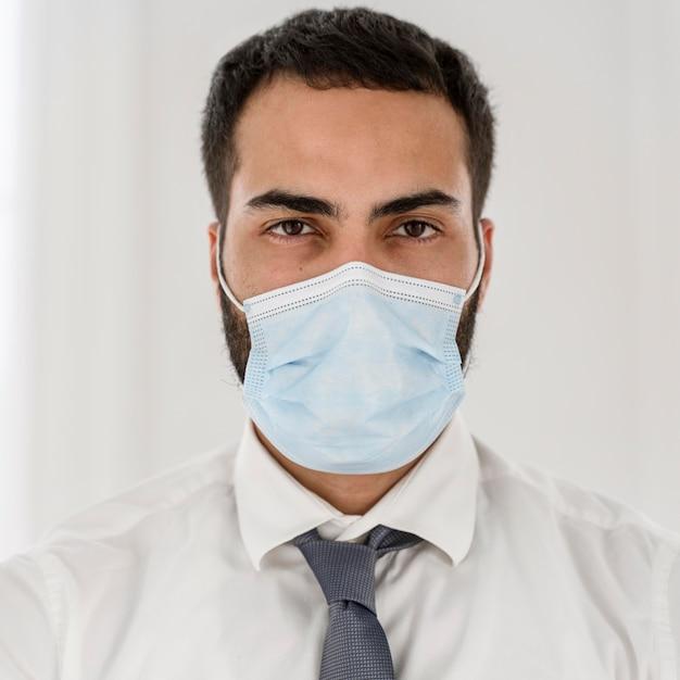 Портрет молодого врача в медицинской маске Premium Фотографии