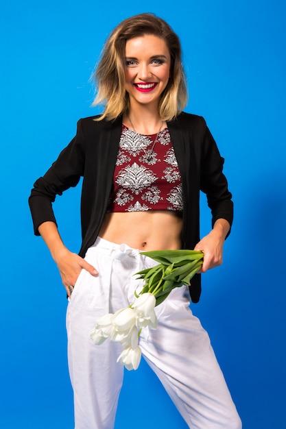 白い花を持って明るいメイクと暗いブレザーのエレガントな若い女性の肖像画 無料写真