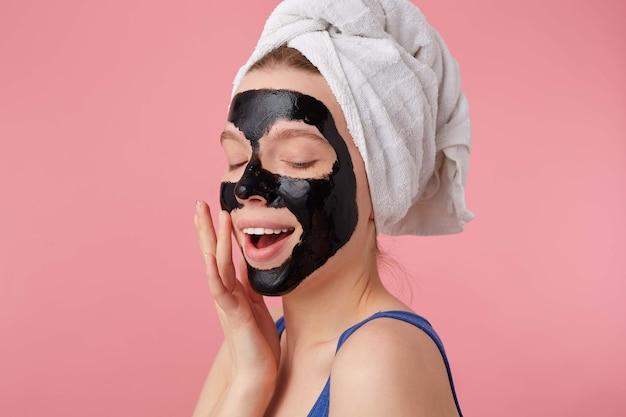Портрет молодой женщины наслаждаясь после душа с полотенцем на голове, с черной маской, касается лица, стоит. Бесплатные Фотографии