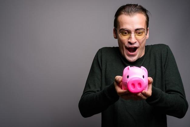Портрет молодого возбужденного человека, держащего копилку Premium Фотографии