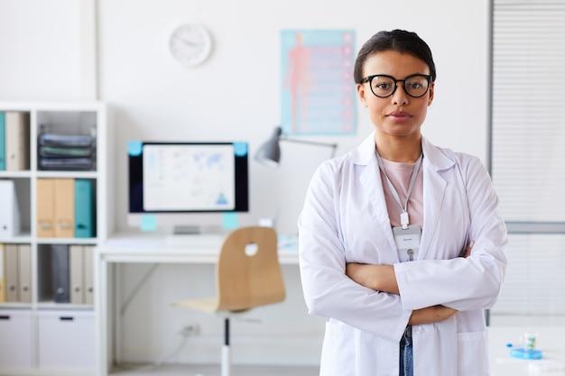 彼女の腕を組んでオフィスで立っている眼鏡の若い女性医師の肖像画 Premium写真