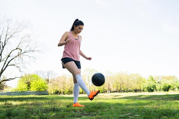 Портрет молодой женщины-футболиста тренировки и практики на футбольном поле Бесплатные Фотографии