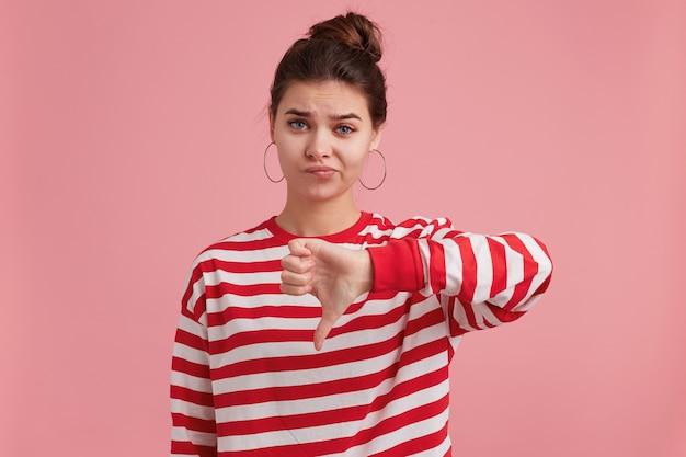 Портрет молодой девушки с веснушками, одетой в полосатый длинный рукав, смотрит с неудовольствием, угрюм, дуется и показывает палец вниз от неприязни. Бесплатные Фотографии