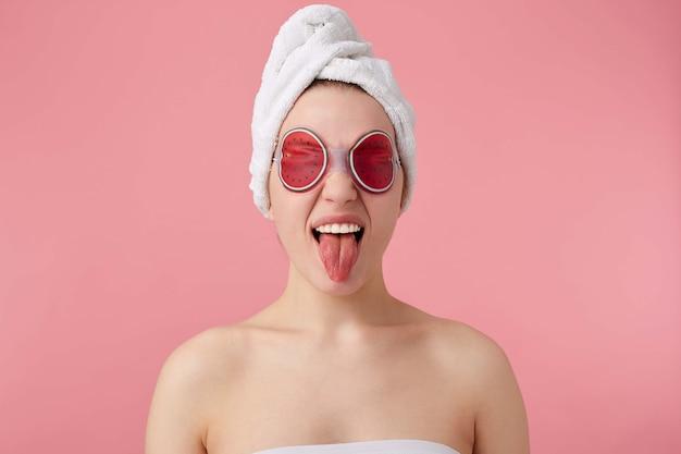 彼女の頭にタオルでシャワーを浴びた後、目の上にマスクを持つ若い面白い女の子の肖像画は、舌と立っています。 無料写真