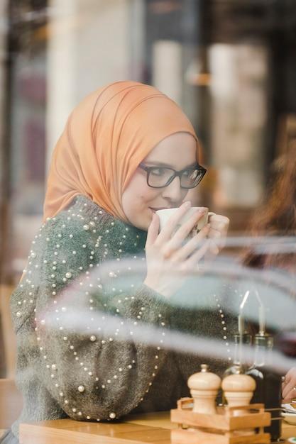 コーヒーを楽しんでいる若い女の子の肖像画 無料写真