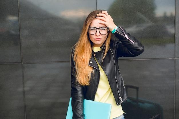 黒眼鏡と黒の背景に外に立っている長い髪の少女の肖像画。彼女は黄色いセーターと黒いジャケットを着ています。彼女は怖がって迷子に見えます。 無料写真