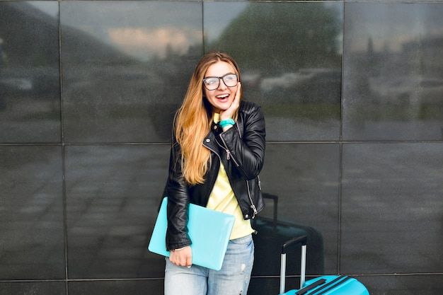 メガネの長い髪の少女の肖像画は、黒の背景に外に立っています。彼女はジーンズと黒のジャケットを着ており、ラップトップを持っています。彼女はカメラに微笑んでいます。 無料写真