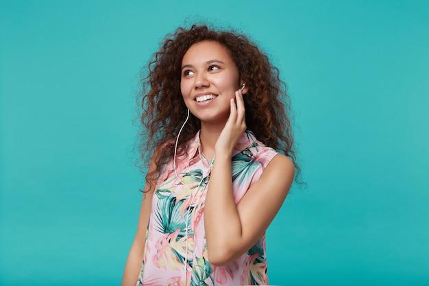 青で隔離、前向きに笑って、音楽を聴きながら彼女の耳に手を上げる若い嬉しい茶色の髪の巻き毛の女性の肖像画 無料写真