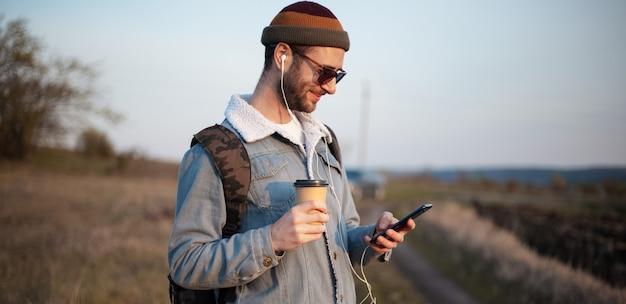 ホットコーヒーと屋外のイヤホンとスマートフォンのカップを保持している若い男の肖像画 Premium写真