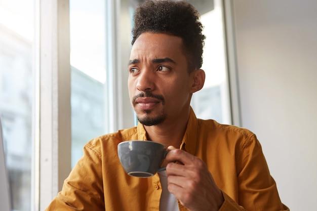 Портрет юного смуглого красавца-сомневающегося бариста пьет ароматный кофе из серой камеры и задумчиво смотрит в сторону, пытаясь ощутить вкус зерна. Бесплатные Фотографии
