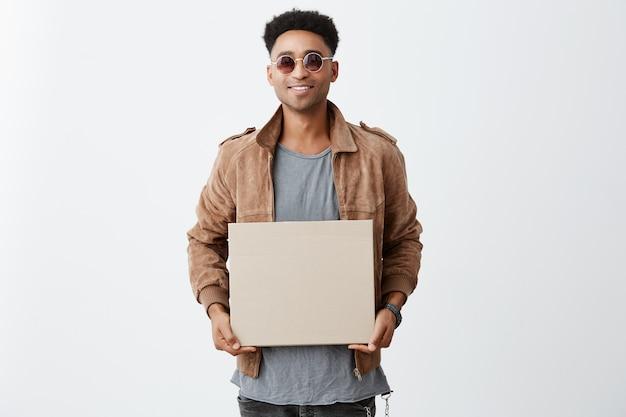 幸せな表情でカメラで探している灰色のシャツ、茶色のジャケット、サングラスを手に明るい笑顔の板紙を手に持つアフロ髪の若いハンサムな浅黒い肌の男の肖像画。 無料写真