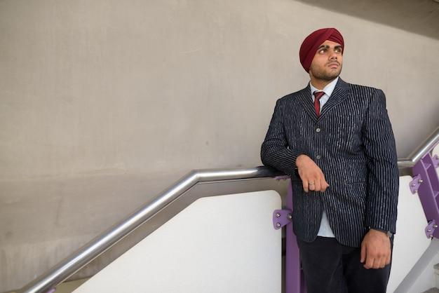 タイのバンコクの街を探索しながらターバンを着ている若いハンサムなインドシーク教のビジネスマンの肖像画 Premium写真