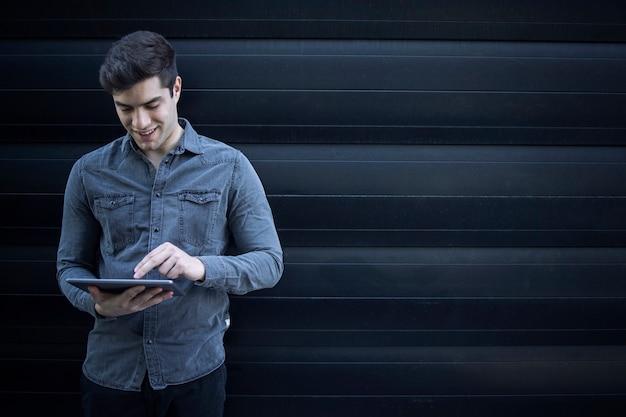 Портрет молодого красивого человека, печатающего на планшетном компьютере и серфинга в интернете Бесплатные Фотографии