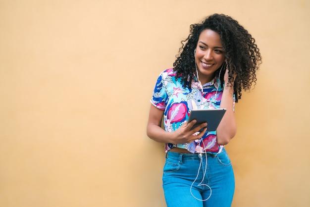 Портрет молодой счастливой афро-американской латинской женщины слушая музыку на ее цифровом планшете. концепция технологии. Premium Фотографии