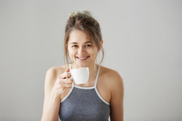 Портрет молодой счастливой красивой женщины усмехаясь держащ выпивая чашку кофе на утре над белой стеной. Бесплатные Фотографии