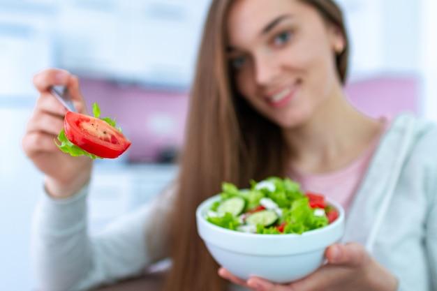 Портрет молодой счастливой здоровой женщины, едят салат из свежих овощей в домашних условиях. чистая и контролируемая пища Premium Фотографии