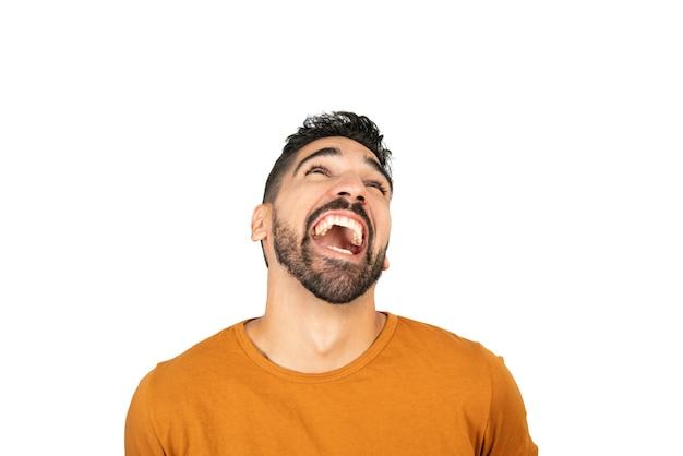 Портрет молодого счастливого человека, улыбающегося против белого пространства Бесплатные Фотографии