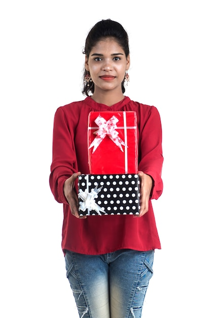 젊은 행복 웃는 여자 잡고 흰색 배경에 선물 상자와 함께 포즈의 초상화. 프리미엄 사진