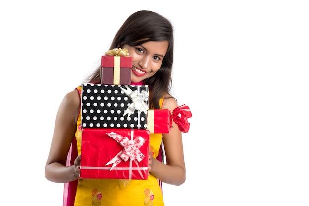 白い壁にギフトボックスを保持している若い幸せな笑顔のインドの女の子の肖像画。 Premium写真