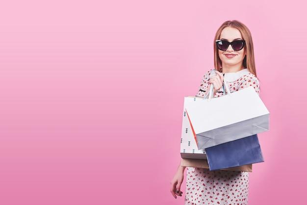 핑크에 쇼핑백과 젊은 행복 웃는 여자의 초상화 프리미엄 사진