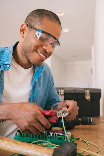 새로운 가정에서 케이블로 전기 문제를 해결하는 젊은 라틴 남자의 초상화. 수리 및 개조 홈 개념. 프리미엄 사진