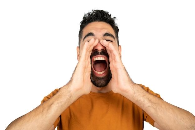 Портрет молодого латинского человека кричать и кричать на белом фоне в студии. Premium Фотографии